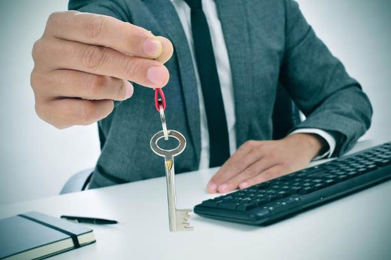 Mann hält Schlüssel entgegen