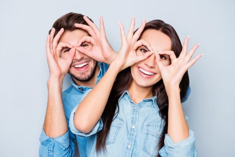 Junges Paar hält sich mit Händen wie eine Brille vors Auge